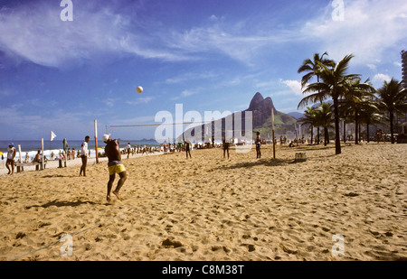 Rio de Janeiro, Brazil. People playing volleyball on Ipanema beach with the Dois Irmaos and palm trees. - Stock Photo