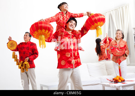 Family putting up Chinese New Year decorations - Stock Photo