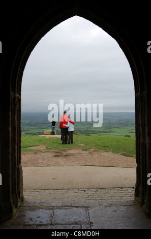 Tourists pose for pictures at the summit of Glastonbury Tor. - Stock Photo