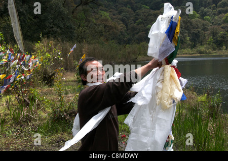 Adjusting prayer flags Khecheopalri Lake Sikkim India - Stock Photo