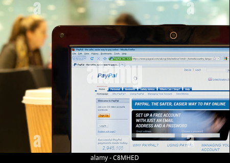The PayPal website shot in a coffee shop environment (Editorial use only: print, TV, e-book and editorial website). - Stock Photo