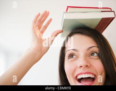Brazilian woman balancing books on her head - Stock Photo