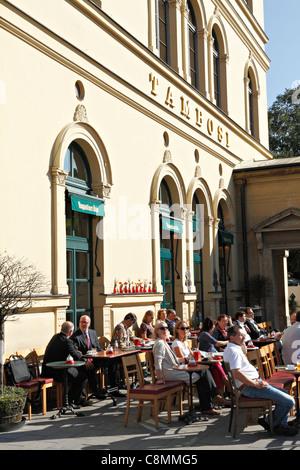 People sitting outside in the sun at Cafe Tambosi Odeansplatz, Munich Upper Bavaria Germany. Europe - Stock Photo