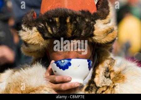 A Kazakh eagle hunter drinking a warm cup of milk tea. - Stock Photo