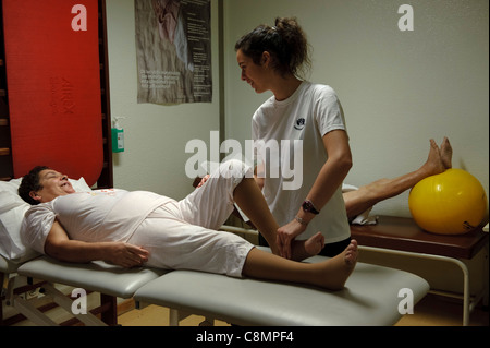 Female physiotherapist helping a patient do an exercise Stock Photo