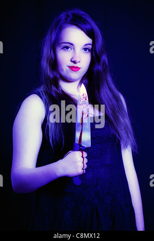young woman with a bloody knife - Stock Photo