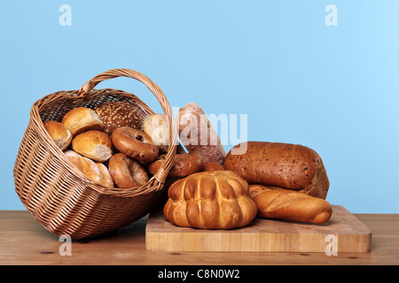 Photo of various types of bread loaves and rolls in a wicker basket on a wooden table with blue background. - Stock Photo