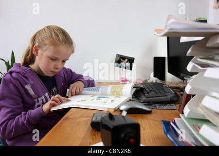 Girl, 10 years old, learning for school, at home in her room, doing homework. - Stock Photo