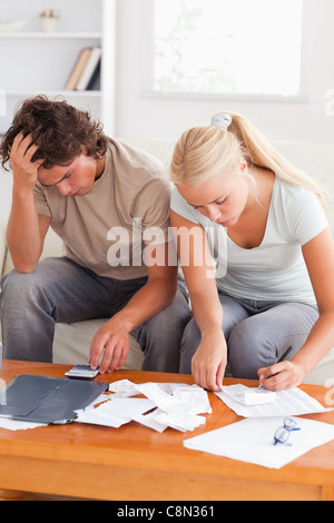 Despaired couple calculating their expenses - Stock Photo