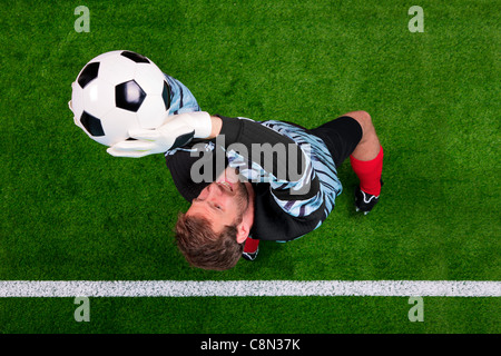 Overhead photo of a football goalkeeper jumping in the air saving the ball on the line. Focus point is on his face. - Stock Photo