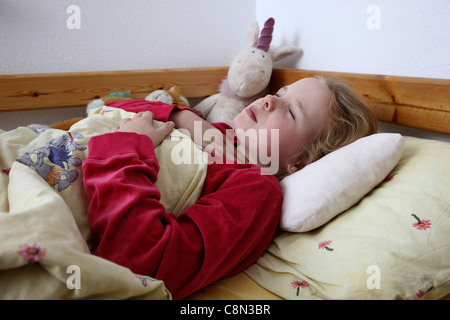 Young girl, 10 years old, lies sick in bed with a flu. Having a sore throat. - Stock Photo