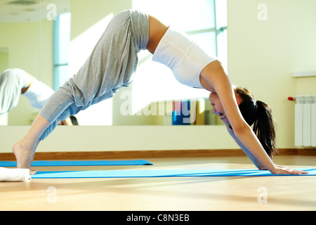 Portrait of young girl doing physical exercises in gym - Stock Photo