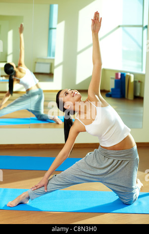 Portrait of young sporty girl doing physical exercise on stretching - Stock Photo