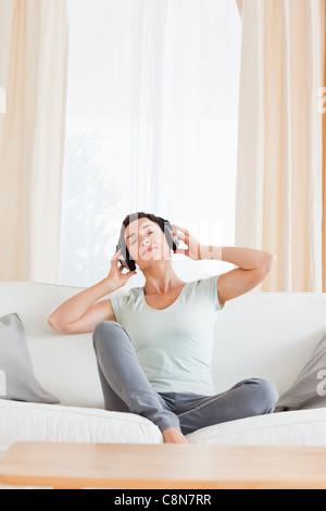 Portrait of a brunette enjoying some music - Stock Photo