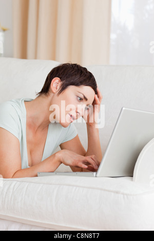Tired young woman using a laptop - Stock Photo