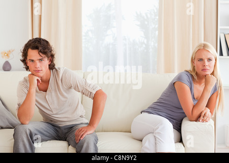 Upset couple sitting on a sofa - Stock Photo