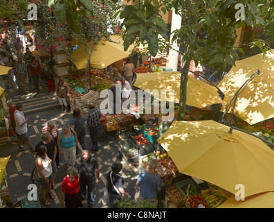 People tourists visitors walking by the fruit and vegetable stalls at the farmers market Mercado dos Lavradores Funchal Madeira Portugal EU Europe
