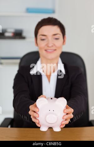 Portrait of an office worker holding a piggybank - Stock Photo