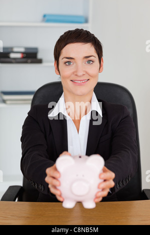 Portrait of a smilling office worker holding a piggybank - Stock Photo