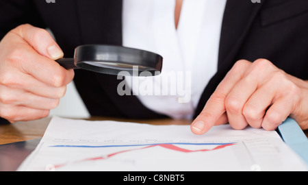 Female hands holding a magnifying glass above a chart - Stock Photo