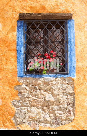 Italy, Sardinia, Fonni, window with grate and window box containing red geraniums - Stock Photo