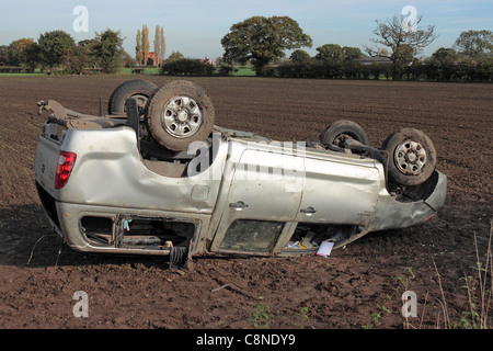 A 4 wheel drive fails to negotiate a bend on a country road and ends up on its roof in a field - Stock Photo