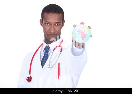 Doctor holding globe - Stock Photo