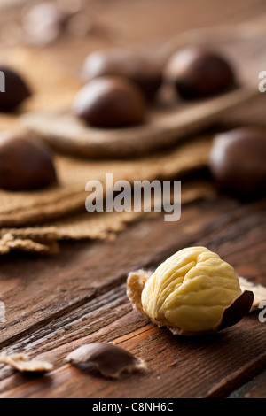 Raw Chestnuts on Wood with Jute and Wooden Spoon - Stock Photo