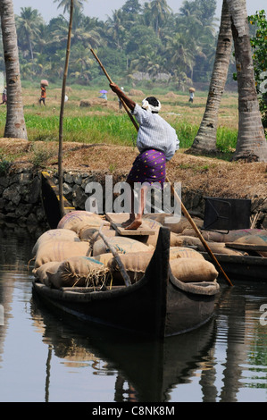 Man poling an 'original' rice boat with rice sacks collected from the paddy fields in the rice belt area of Kerala - Stock Photo