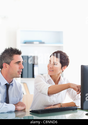 Woman pointing at something to her colleague on a screen - Stock Photo