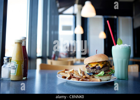 Cheeseburger, french fries and milkshake in diner - Stock Photo