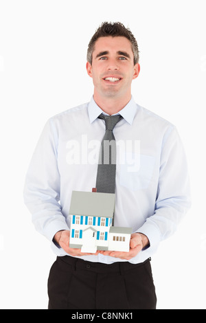 Businessman holding a miniature house - Stock Photo
