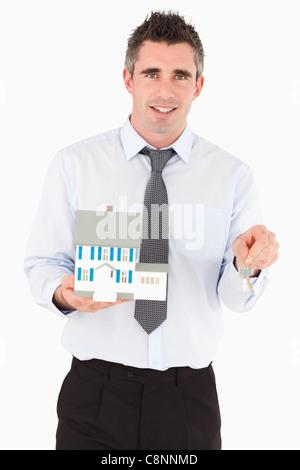 Businessman holding a key and a miniature house - Stock Photo