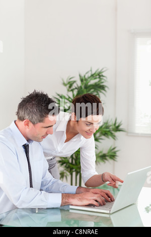 Portrait of a woman pointing at something to her colleague on a laptop - Stock Photo