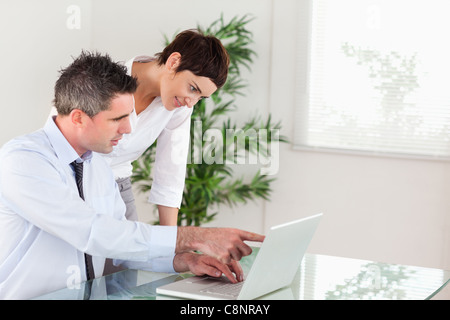 Businessman pointing at something to his colleague on a laptop - Stock Photo