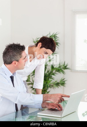 Portrait of a man pointing at something to his colleague on a laptop - Stock Photo