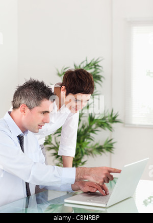 Portrait of a man pointing at something to his colleague on a notebook - Stock Photo