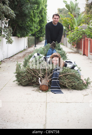 Caucasian couple dragging Christmas tree in alley - Stock Photo