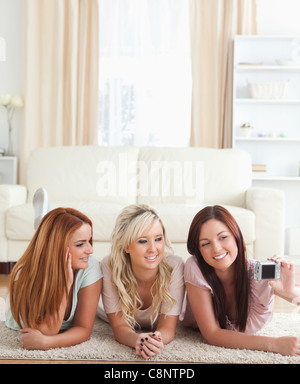 Cheerful women lying on the floor taking a picture - Stock Photo