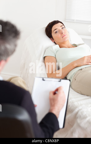 Psychologist talking to a sad female patient - Stock Photo