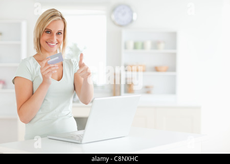 Blonde woman with credit card and notebook holding thumb up - Stock Photo