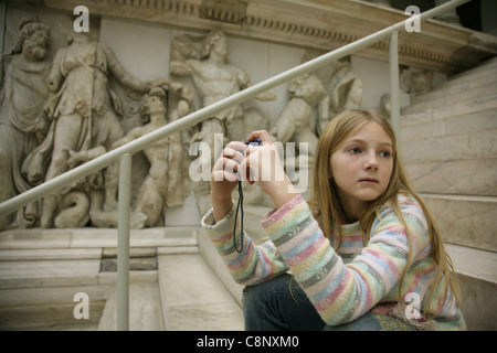 Young visitor sits in front of the Pergamon Altar in the Pergamon Museum in Berlin, Germany. - Stock Photo