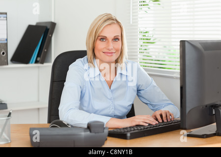 Working woman in front of a screen looks into camera - Stock Photo