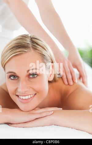 Close up of a smiling woman relaxing on a lounger during a massage - Stock Photo