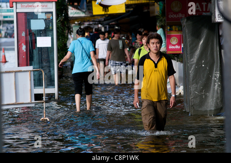 Bangkok residents wade through the flood on Phahon Yothin Road, Bangkok, Thailand on October 28th, 2011. Thailand - Stock Photo