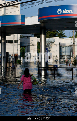 Thai woman wades through flood waters, Phahon Yothin Road, Bangkok, Thailand, South East Asia on October 28th, 2011. - Stock Photo