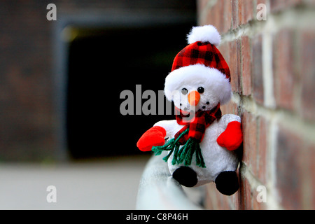 A toy snowman on a pole leading into a tunnel - Stock Photo