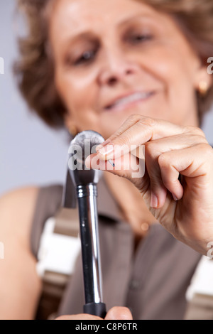 Senior woman with a hammer driving a nail - Stock Photo