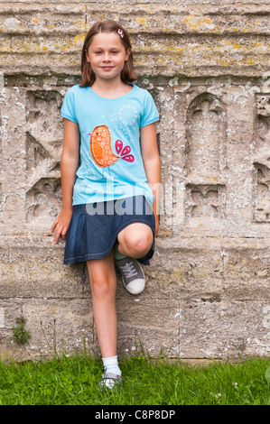 A ten year old girl outside in a churchyard in the Uk - Stock Photo