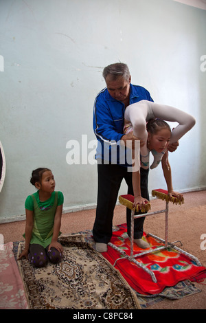 Coach helping young contortionist girl with her legs over her head while another girls looks on - Stock Photo